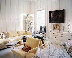 Living Room Photo - A yellow patterned couch and a pair of yellow chairs in a white living space