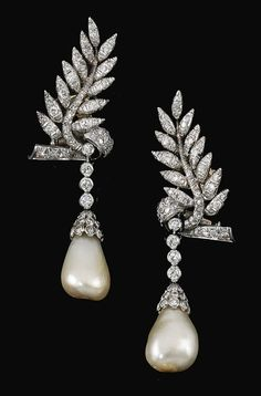 PAIR OF NATURAL PEARL AND DIAMOND PENDENT EARRINGS. Each surmount designed as a leaf set with circular-cut diamonds, suspending a drop-shaped natural pearl from a line of diamonds, post and screwback fittings.