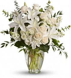 Beautiful flowers such as white hydrangea, spray roses and stock, peach roses, eucalyptus and more fill a tall glass vase.