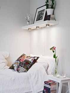 White Bedroom with Stool as Nightstand and High Floating Shelf