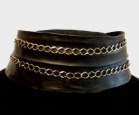Korppi-sarjan kaulakoru Mustaa, muokkaamatonta nahkaa eli pergamenttia sekä patinoitua hopeaketjua.