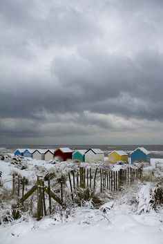 snow covered beach huts with fence in foreground by Adnams, via Flickr