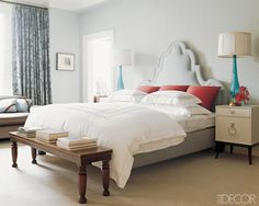 pale blue and white bedroom with  dark wood and black accents and pops of red