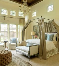 Sophisticated, old-world style and contemporary design merge in comfortable elegance in this master bedroom. Classic pieces such as an antique daybed and iron four-poster blend harmoniously with a leather headboard and shimmery silk fabrics.