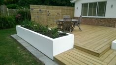 A contemporary deck with raised planters and slatted privacy trellis by SilverBirch Gardens Ltd