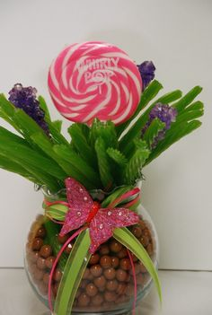 The jar contains brown chocolate sixlets and is filled with green apple licorice, rock candy sticks, and a large whirly pop to top it off.  It is accented with color coordinating ribbons as well.