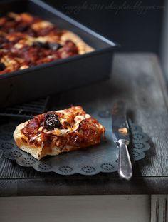 Sfincione jest rodzajem grubego, puszystego placka, który dawniej rolnicy sycylijscy zabierali ze sobą do pracy. Podobno początkowo był to kawałek ciasta zapieczonego w piecu z oliwą, solą, czasem serem. Niektórzy twierdzą, że nie powinien zawierać sosu pomidorowego, inni, że i owszem. Jedni pieką go w prostokątnych blachach, inni w formie grubych placków. Najczęściej spotykana wersja to taka, która zawiera duszoną cebulę, filety anchovies, oregano, ser Caciocavallo i chlebowe okruchy…