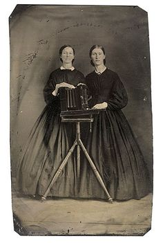 19th-century:  Portrait of two women and a camera.Tintypec.1870's