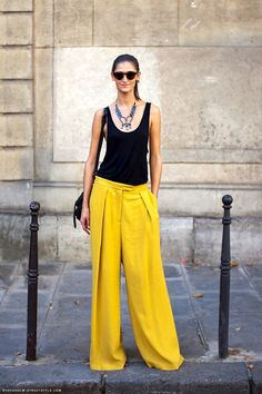 Black simple tank tucked into yellow palazzo pants