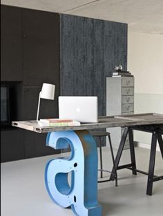 A big metal letter, probably from an old outdoor sign, and a recycled door, make a totally cool industrial desk in this home office space. Big A! I'm digging this! Glass instead of a door though! #mderr