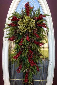 just love this!! This design is so warm and welcoming with a natural feel. I used a teardrop pine swag and filled it with pine moss foliage, red berries, dark green berry branches, and pine cones. Then I topped it off with sage green hydrangeas
