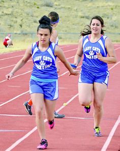 Rose Archuleta, right, hands the baton off to Esperanza Gonzales during the 4x100 meter relay at Cimarrón. Photo courtesy JR Rael