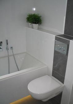 Witte badkamer met bruine banen in de tegelwanden en verlichting onder het bad. De bruine banen zijn van dezelfde tegels als op de vloer.