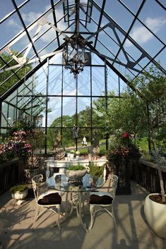 A greenhouse is used for morning tea. The planters at left and right were made from ironwork that came from a mosque in Pittsburgh that was torn down; Ms. Dormer and Ms. Dagnal found them at a local salvage company. The iron gate came from an estate sale. The wooden scrolls came from a flea market in France.
