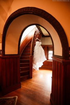 wedding dress hanging on a spiral staircase at belhurst castle in geneva ny