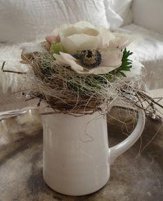 Kanne mit Zweigen und Blüten