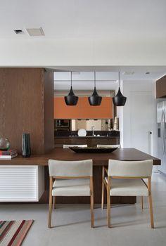 Madeira escura e toques de laranja dão o tom desta cozinha, localizada em um apartamento criado para um pai e sua filha. Veja os outros ambientes no site da Casa Vogue