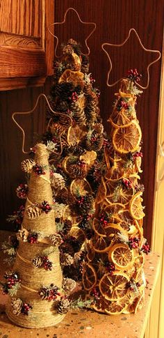 ~` trio of trees decorated with pine cones dried oranges and christmas sprigs . copper stars add the finishing touch! `~