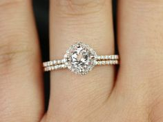 This wedding set is designed for those who love simple with a slight twist. The round cut in the center is traditional while the cushion halo gives it