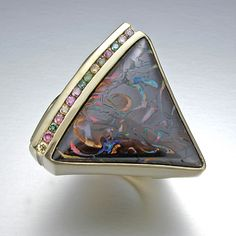 Ring   Vickie Riggs.  14kt yellow gold and boulder opal. Drawing out the opal's intense and dramatic colors are 15 multicolored fancy diamonds
