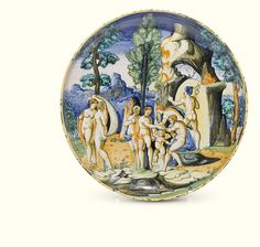 AN URBINO ISTORIATO DISH, DURANTINO WORKSHOP, CIRCA 1545 painted with the Judgement of Paris, after Marcantonio Raimondi, Paris presenting the apple of discord to Aphrodite as Hermes leaves through a natural arch, Hera and Athene turning aside, a mountainous lakeside town beyond, the reverse inscribed 'Senntéziia de Paris' D. 26 cm,
