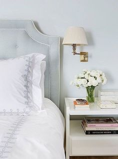 Love the classic look of this baby blue tufted headboard paired with the lavender-trimmed crisp white sheets!