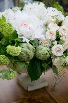 centerpieces including apples, artichokes, succulents, and ornamental kale for added dimension.