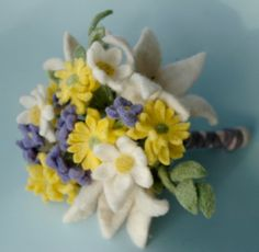 This is the first felt bridal bouquet I made with white lillies, yellow mums, daisies, and a little periwinkle blue flower I invented.  By Julie Rosenthal www.aspencroft.ca