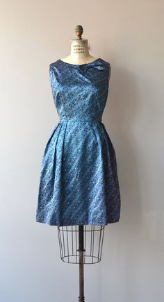 Vintage 1950s, early 1960s french blue metallic party dress with metallic gold centered flowers, bateatu neckline with small bow at one side, fitted