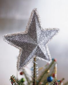 The traditional Christmas star becomes a shimmering beacon when coated with silver glitter and outlined with wired tinsel roping.