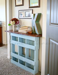 A maple-stained board atop a chalk-painted pallet becomes the perfect platform for your living room odds and ends. See more here.   - CountryLiving.com