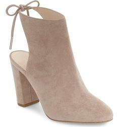 This striking almond-toe bootie stands out with a daring cutout heel fastened with a dainty leather bow.