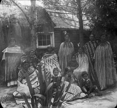 Group of Maori men, women and children, wearing Maori cloaks, circa 1900. Chief Te Taupua is seated on the left
