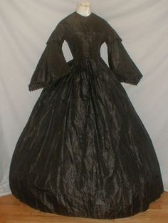 """Splendid 1860's Civil War Black Silk Mourning Dress  eBay- fiddybee; over sleeve & hem of sleeve trimmed with black silk & black chenille velvet balls, same with bodice front, piping at neck, armscyes & waist; bodice cotton lined with front hook & eye closure, skirt attached w/ cartridge pleating, unlined except band of cotton at hem; some underarm discoloration on lining; some small holes & splits; bust: 34""""; waist: 26""""; skirt length: 42""""; width at hem: 144"""""""