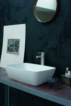 Black bathroom with round mirror and artwork. Minimal sink for a trendy bathroom. Clearwater baths.