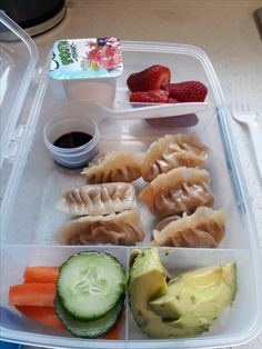 Pork and ginger dumplings (with carrots and spring onions) with soy sauce (dipping), avocado, cucumber and carrot, strawberries and yogurt.