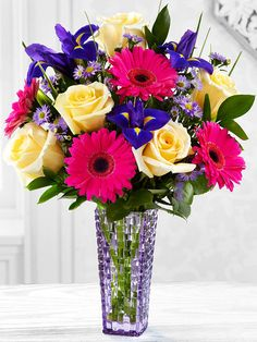 Roses and cheery gerbera daisies. Yellow roses, hot pink gerbera daisies, purple Monte Casino asters, purple iris, and lush greens are brought together to form an eye-catching flower bouquet presented in a designer purple glass vase.