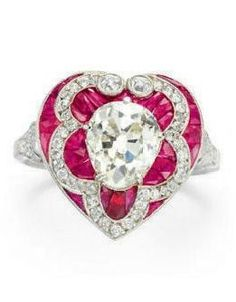 AN ART DECO DIAMOND AND RUBY RING. Centring upon an old mine-cut diamond, within a vari-cut ruby and old European-cut diamond heart-shaped surround, to the pierced old European-cut diamond shoulders, mounted in platinum, circa 1920.