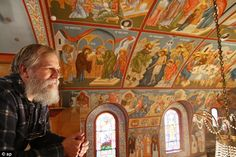 Artist's work: Iconographer and Reverend Theodore Jurewicz looks over the icons he's painted over the last six years, which totally cover the interior of the St. Stephen Serbian Orthodox Church in Lackawanna, New York on Monday