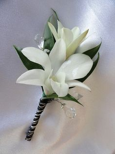 Two White Dendrobium Orchid florets and Italian Ruskus with Crystals and a Black & Silver ribbon wrap | Walden Floral Design