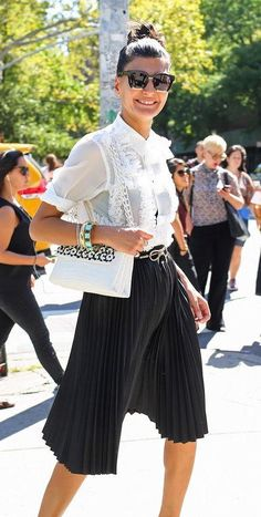 Giovanna Battaglia in a black pleated skirt and a lace white top