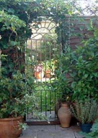 A long mirror attached to a wall in which an applied lead design is made to resemble a wrought iron gate.  What you see in the mirror is a reflection of the garden IN FRONT of the mirror, not a gate, in which you are looking through to see the garden.
