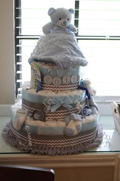 """This 3 tier diaper cake will be the perfect centerpiece at your baby shower! This cake comes with Pampers Swaddlers Diapers  and measures 18"""" tall, plus the height of any ornaments on top!"""