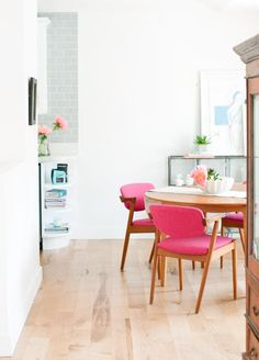 Modern dining room with pop of bright pink chairs.