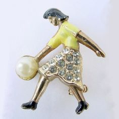 A cute little pin made in the shape of a woman bowler with a yellow painted blouse, black painted hair and shoes, a  rhinestone skirt and faux pearl bowling ball. The unpainted areas have a copper col