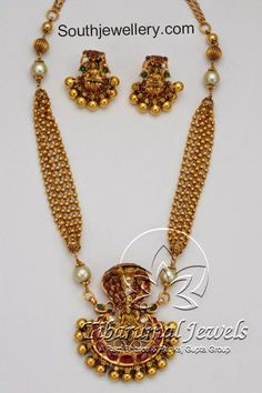 A creative design with 22 carat gold antique finish multi strings gold balls chain attached to nagarm pendant embossed with Goddess Lakshmi at the center, studded with rubies, flat diamonds, south sea pearls and emeralds. The necklace is paired up with matching temple Lakshmi earrings. For inquiries contact: sales@tibarumal.in Website: www.tibarumal.in Shop Address: Tibarumal Jewels …