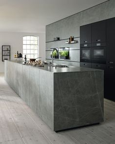 Architonic The generously sized kitchen island with ceramic marble decor is a design statement for this modern and open room layout. It opens up to the living and dining room and offers new ideas for homely furnishings. The spacious island with the minimalist, thin countertop almost seems chiselled out of one piece – the tall unit of matt black glass creates visual calm. #next125 #modernkitchendesign #interiordesign #openkitchendesign #ceramickitchendesign #storageideas #wallkitchenpanel