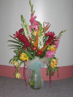 Tropical arrangement with Birds of Paradise, Ginger, Gladiolas, Snapdragons, Parrot Tulips, Aster, Hanging Amaranthis, and misc. greens.