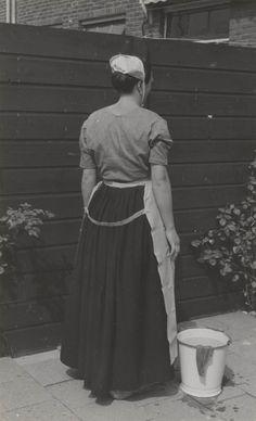 Vrouw in Scheveningse streekdracht. De vrouw is gekleed in de daagse werkdracht anno 1953. Ze draagt een jak van lichtblauw verpleegsterslinnen, een zwarte rok en een wit met blauw geruite schort. Op het hoofd draagt ze het 'nachtmutsje'. #ZuidHolland #Scheveningen