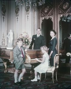 Queen Elizabeth, Prince Phillip, Prince Charles and Princess Anne standing around a piano, Ottawa, October 1957.